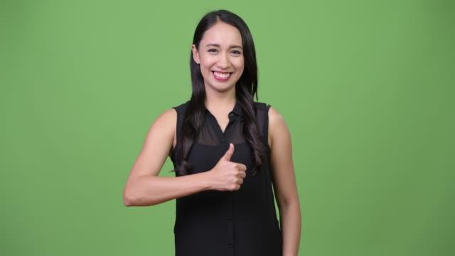 young beautiful asian businesswoman giving thumbs up - филиппинского происхождения стоковые видео и кадры b-roll