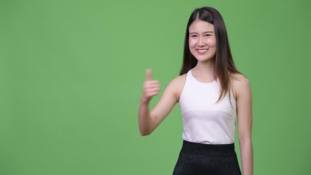 vídeos y material grabado en eventos de stock de joven empresaria asiática hermosa dando pulgares - sudeste