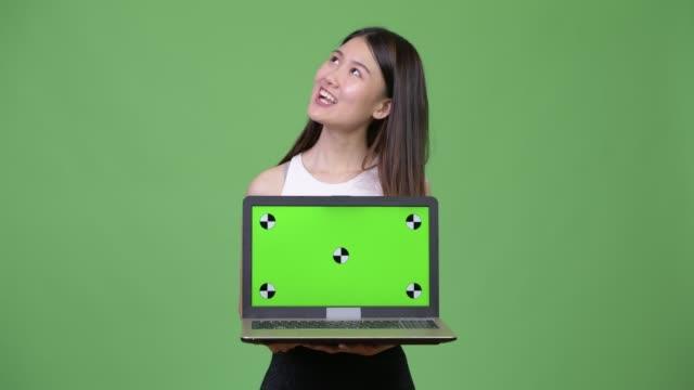 young beautiful asian businesswoman showing laptop - юго восток стоковые видео и кадры b-roll