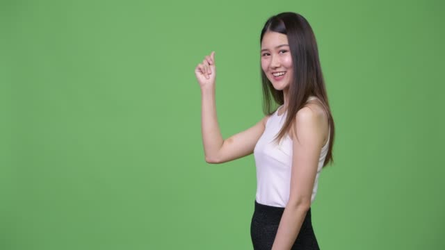 Young beautiful Asian businesswoman showing something Studio shot of young beautiful Asian businesswoman against chroma key with green background snapping stock videos & royalty-free footage
