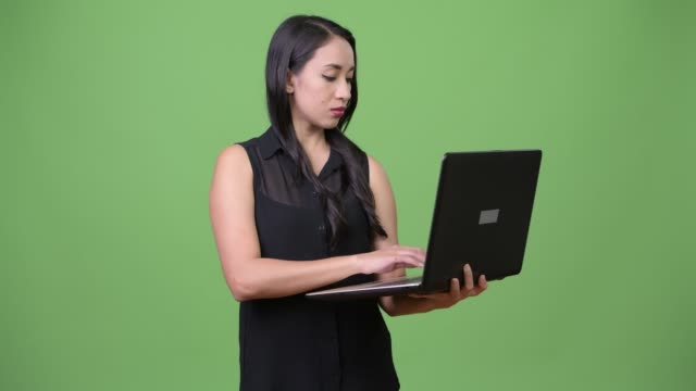Young beautiful Asian businesswoman using laptop Studio shot of young beautiful Asian businesswoman against chroma key with green background southeast stock videos & royalty-free footage