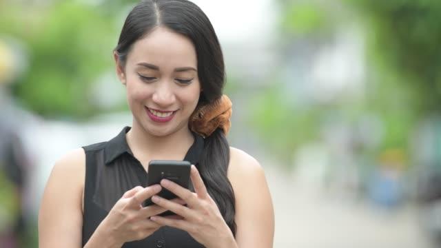 young beautiful asian businesswoman using phone in the streets outdoors - филиппинского происхождения стоковые видео и кадры b-roll