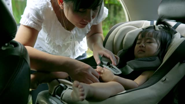 young Beautiful Asian mother unbuckling her baby daughter from her car seat video