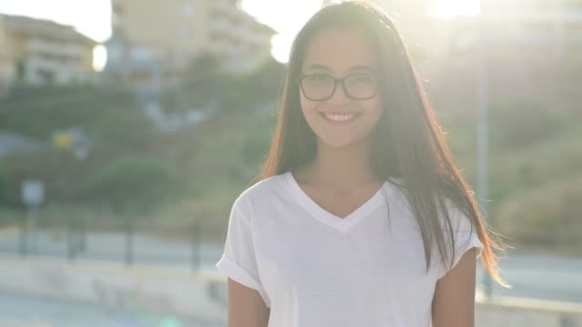 Mulher asiática nova do turista que sorri de encontro à luz solar na estação de caminhos-de-ferro - vídeo