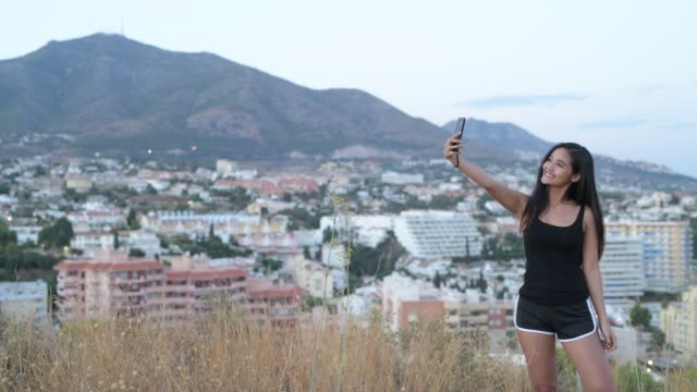 Young Beautiful Asian Tourist Woman Smiling While Taking Selfie On The Hill