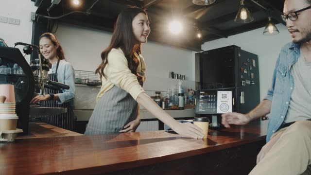 Young beautiful Asian woman barista wear apron holding hot coffee cup served to customer at bar counter in coffee shop with smile face.Concept of cafe and coffee shop small business.