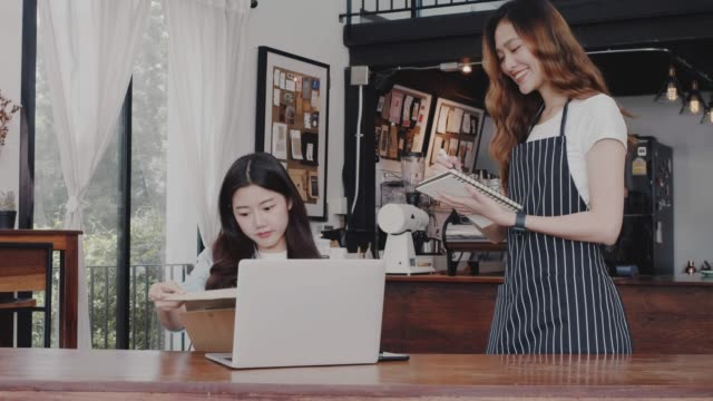 Young beautiful Asian woman barista wear apron receive coffee order from customer at table in coffee shop with smile face.Concept of cafe and coffee shop small business.