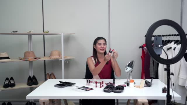 Young beautiful Asian woman beauty makeup vlogger influencer explaining cosmetic product lipstick on social media live video. Online shopping business advertising by blogger or influencer concept.