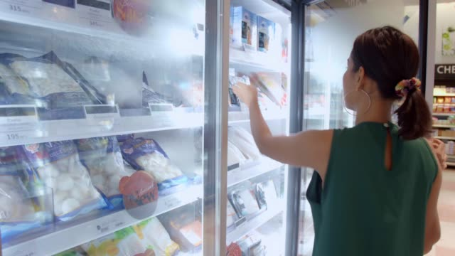 young beautiful asian woman buying fresh frozen seafood at the grocery store supermarket. - замороженные продукты стоковые видео и кадры b-roll