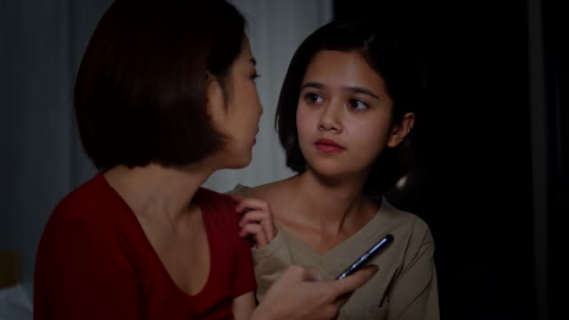 4K Young beautiful Asian woman comforting her sad friend that get bad news from smartphone. Woman hugging and consoling her depressed girls friend at night. Teenage problems and friendship concept.