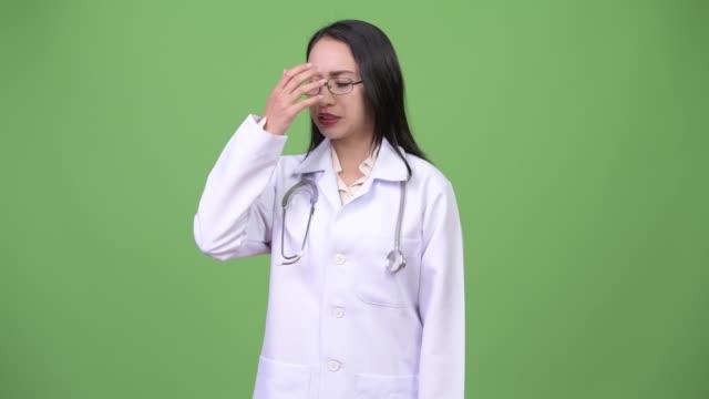 年輕美麗的亞洲婦女醫生頭痛 - 東南 個影片檔及 b 捲影像