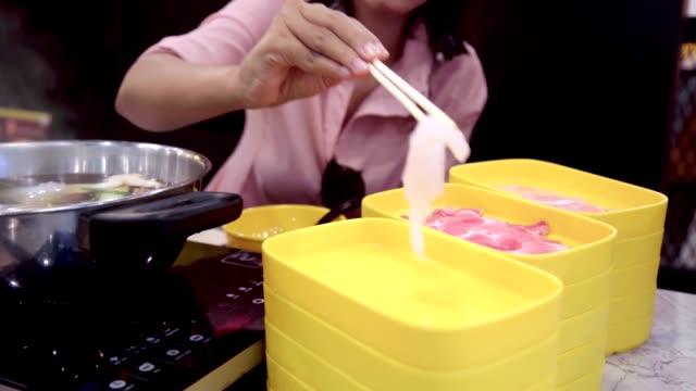 Young Beautiful Asian Woman Eating Shabu Sukiyaki Hot Pot in the Restaurant.