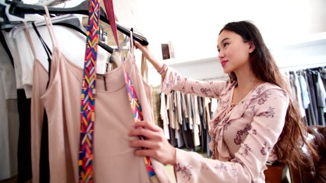 Young beautiful asian woman shopping clothes in a clothing store video