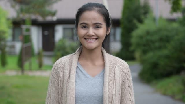 Mulher asiática bonita nova que sorri em casa ao ar livre - vídeo