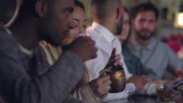 vídeos de stock, filmes e b-roll de jovem mulher asiática linda tomar um gole de sua bebida alcoólica, enquanto conversava com um homem num bar - costumer
