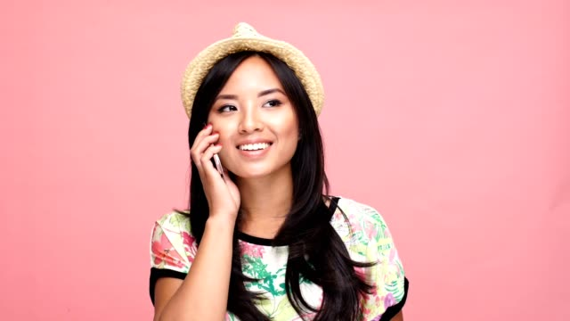 Young beautiful asian woman wearing hat talking by phone over pink background. video