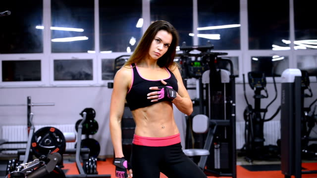 Young beautiful athlete woman in gym showing her muscles. video