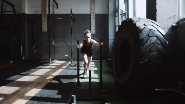 vídeos de stock e filmes b-roll de young beautiful athletic caucasian woman pushing training sled towards camera, exercising in hardcore gym slow motion. - dureza
