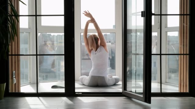 Young beautiful athletic woman blonde in white sportswear doing yoga and stretching on the balcony at home. Stands on the fingers and performs dance steps. Young beautiful athletic woman blonde in white sportswear doing yoga and stretching on the balcony at home. Stands on the fingers and performs dance steps. Concept of home sport and active lifestyle. lotus position stock videos & royalty-free footage