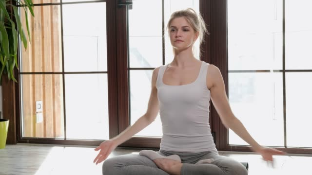 a young beautiful athletic woman blonde sits on the floor and breathes her arms folded across her chest. - gambe incrociate video stock e b–roll