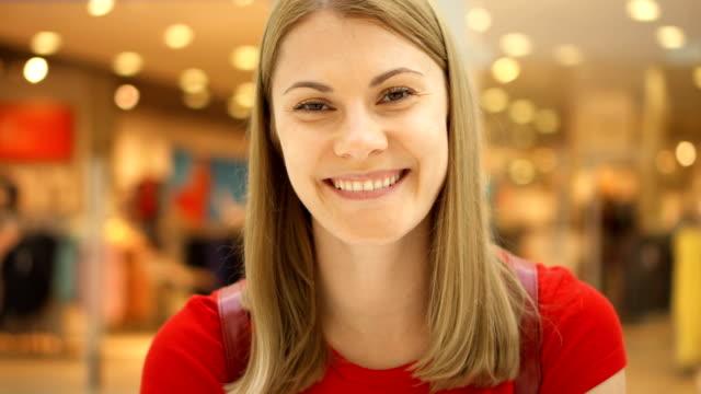vídeos y material grabado en eventos de stock de hermoso atractivo joven en centro comercial, sonriendo. concepto de consumismo comercial - moda playera