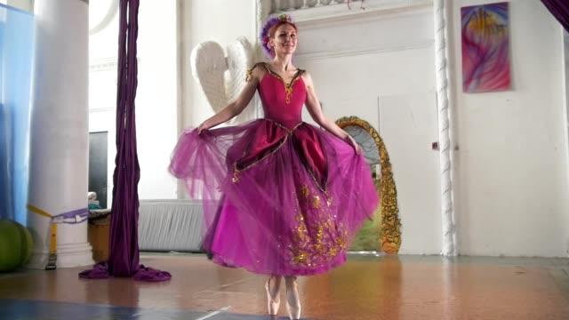 vídeos de stock e filmes b-roll de young beautiful ballerina in purple dress performs dance in spacious white studio - tule têxtil