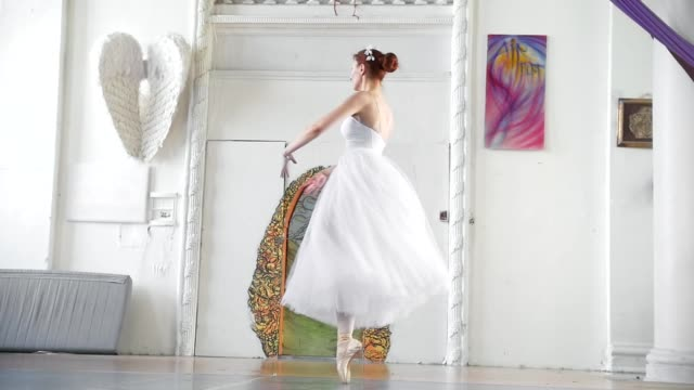 Young beautiful ballerina in white dress performs dance in spacious white studio Young beautiful ballerina in white dress performs dance in spacious white studio, slow motion tulle netting stock videos & royalty-free footage