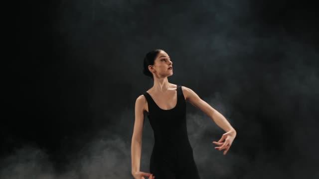 junge schöne ballerina auf rauch bühne tanzen modernes ballett im dunkeln. frau im schwarzen kostüm führt in szene. sinnliche erstaunliche tanz. kunst-konzept. slow-motion - ballettröckchen stock-videos und b-roll-filmmaterial