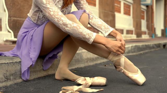 junge schöne ballerina setzt auf spitze schuhe entlang der straße - ballettschuh stock-videos und b-roll-filmmaterial