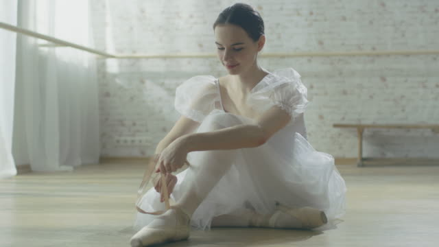 young beautiful ballet dancer sitting on the wooden floor in her tutu dress and tying her pointe shoes. in slow motion. - tutù video stock e b–roll