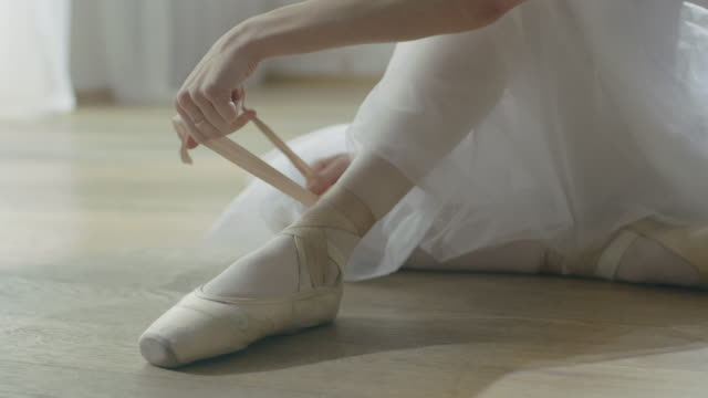 Young Beautiful Ballet Dancer Sitting on the Wooden Floor in Her Tutu Dress and Tying Her Pointe Shoes. In Slow Motion. video