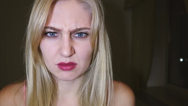young beautiful blond woman with bright blue big eyes and red lips twists her face and turns away from the camera when she sees something nasty, disgust emotion young beautiful blond woman with bright blue big eyes and red lips twists her face and turns away from the camera when she sees something nasty, disgust emotion disgust stock videos & royalty-free footage