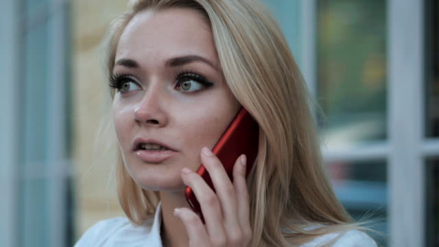 Young beautiful blonde businesswoman talking by cellphone in the city. Woman wearing white shirt. Slow motion video