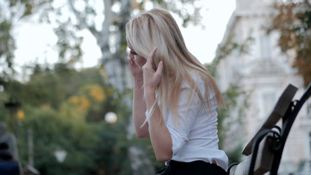 Young beautiful blonde businesswoman talking by mobile phone while sitting on benchin the city. Woman wearing white blouse. Slow motion video