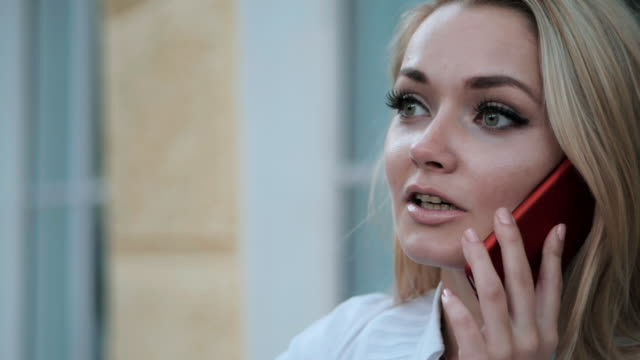 Young beautiful blonde businesswoman talking by smartphone in the city. Woman wearing white blouse. Slow motion video
