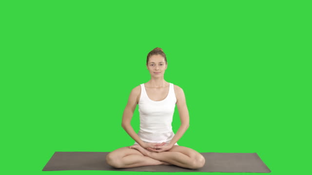 Young beautiful blonde woman doing yoga and smiling on a Green Screen, Chroma Key