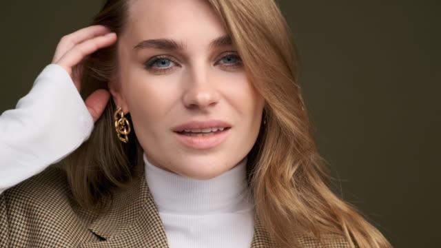 stockvideo's en b-roll-footage met een jonge mooie blonde vrouw in een witte coltrui en de jasje van een man stelt op een groene olijfachtergrond in de studio. - blond haar