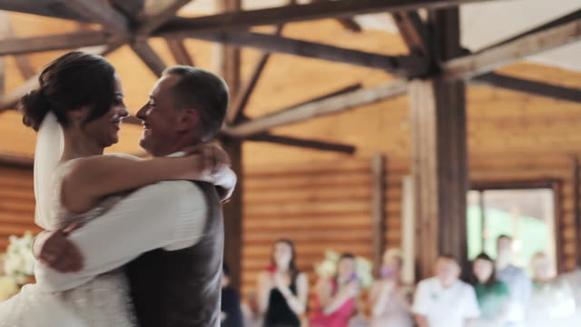 Young beautiful bride and groom dancing first dance at the wedding party. Feel happy