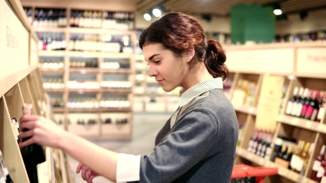 Young beautiful brunette caucasian girl compares two different bottles of wine. Choosing white wine at grocery store video