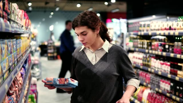 vídeos de stock e filmes b-roll de young beautiful brunette caucasian girl trying to choose cookies at a local grocery store - prateleira compras