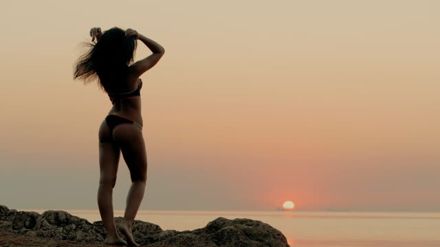 Young beautiful brunette girl in strings swimsuit posing on a stone in ocean. Rocks and sea, sunrise or sunset light, sexy bikini. Attractive seductive sight. Slow motion video