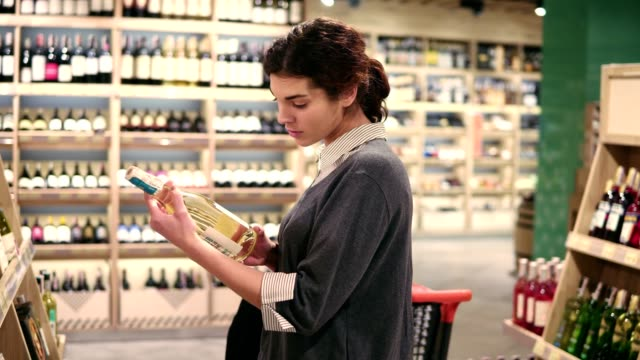 Young beautiful brunette girl picks a bottle of wine from the shelf to read a lable on it. video