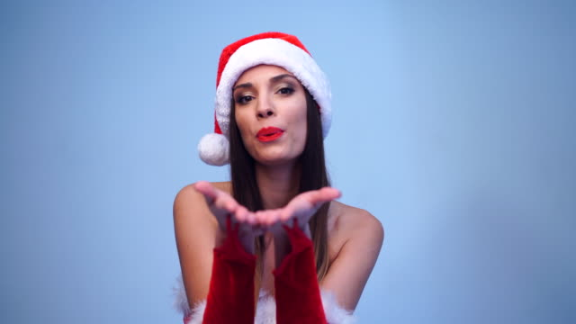 Young beautiful brunette in red dress and Santa Claus hat standing in studio on blue background smiling at the camera.