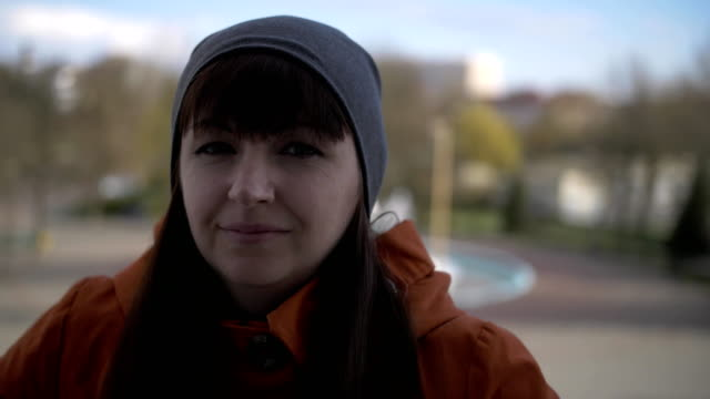 Young beautiful brunette with bangs girl with brown eyes in a gray hat and orange jacket standing on the street, looking straight straightens his cap and smiles sweetly. Close-up shooting glaydtrek video