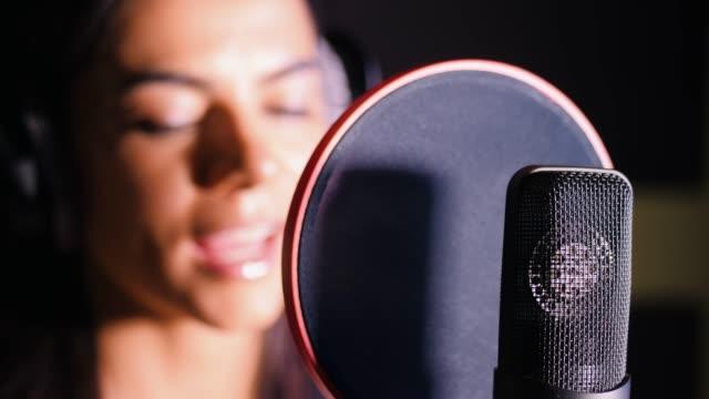vídeos de stock, filmes e b-roll de linda morena jovem gravação da voz, música ou álbum em estúdio profissional. menina canta perto microfone na gravação de quarto sob luz natural. câmera lenta - músico pop