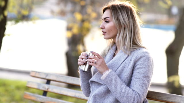 young beautiful business woman drinks alcohol whiskey on nature in the park at sunset after hard work. Autumn background young beautiful business woman drinks alcohol whiskey on nature in the park at sunset after hard work. Autumn background video