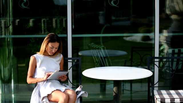 Young beautiful business woman sitting at a table with tablet video