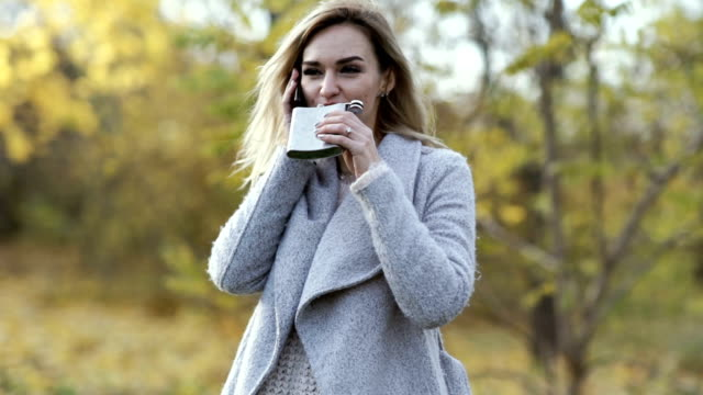 young beautiful business woman talking on the phone and drinks alcohol whiskey on nature in the park at sunset after hard work. Autumn background video