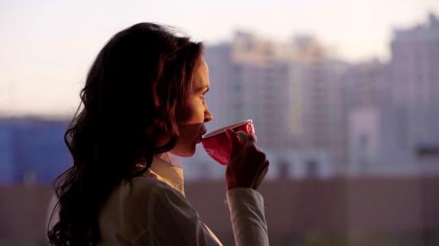 若い美しい実業家都市景観を賞賛し、日没でパノラマの窓の近代的なオフィスでお茶を飲む ビデオ