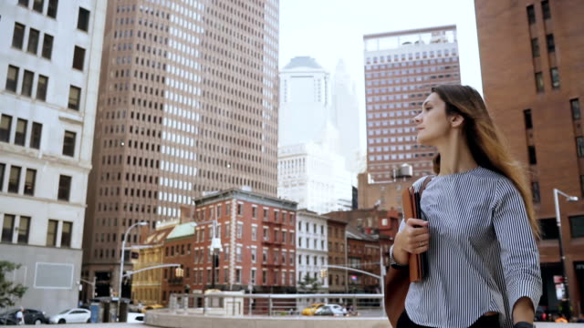 young beautiful businesswoman holding the documents and walking to work in financial district of new york. slow motion - красавица стоковые видео и кадры b-roll